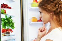 Happy woman and open refrigerator with fruits, vegetables and healthy food