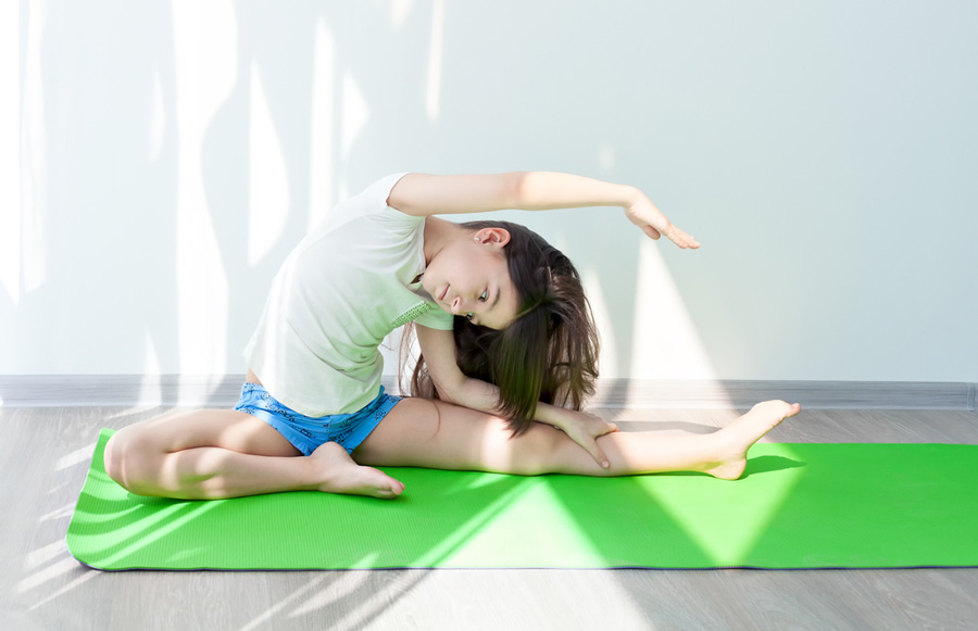 little girl doing gymnastics on a green yoga mat. fitness exercises and stretching. children's fitness and yoga for children.