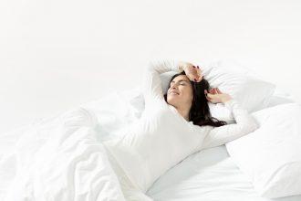 девушка с черными волосами в белой постели